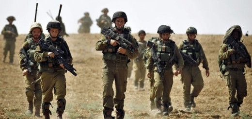 Israeli soldiers from the Nahal Infantry Brigade walk across a field near central Gaza Strip